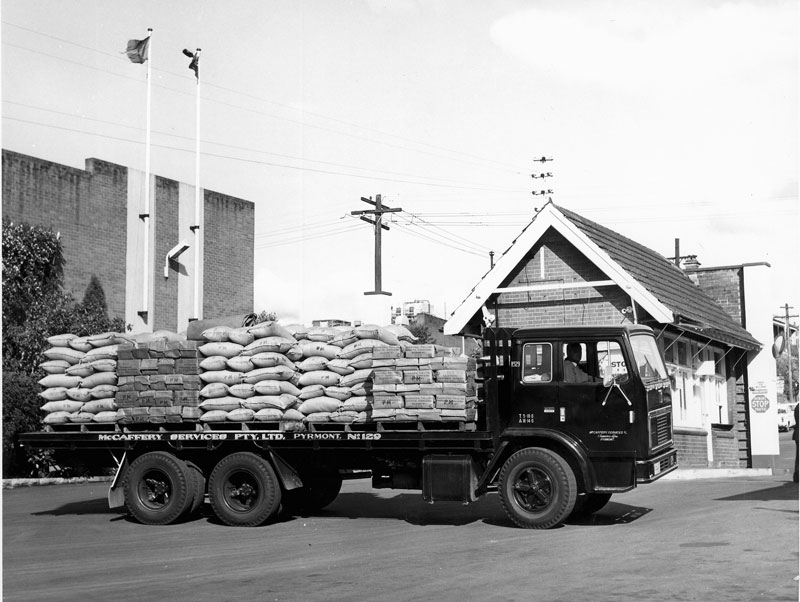 Flatbed of McCaffery Services Pty Ltd, laden with bagged sugar, departs refinery, circa 1960